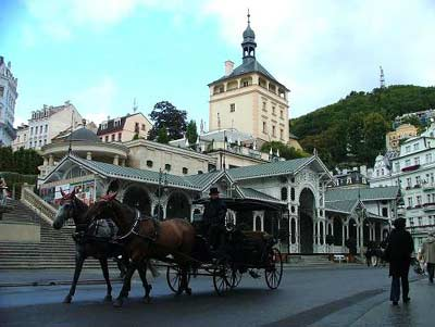 Horse drawn cariage passing the colonnades in Karlovy Vary